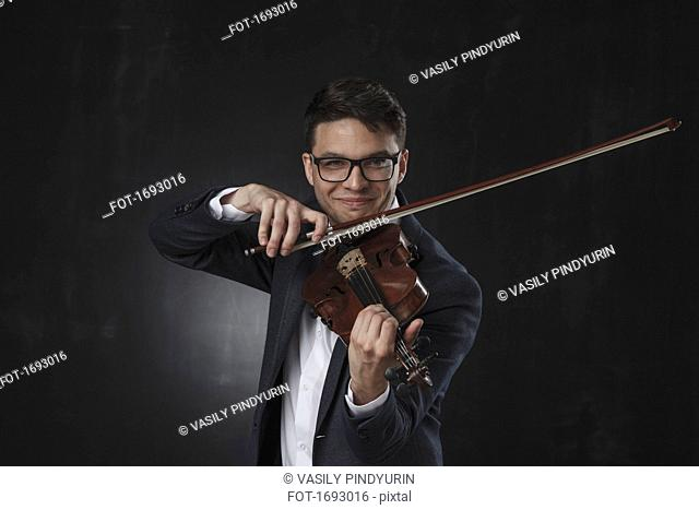 Confident smiling young man playing violin while standing against black background