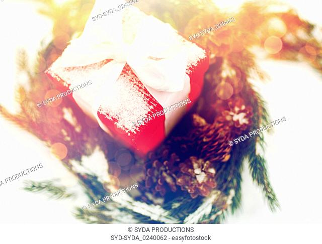 close up of christmas gift and fir wreath on snow