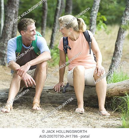 Mature couple sitting on a tree trunk in a forest and looking at each other