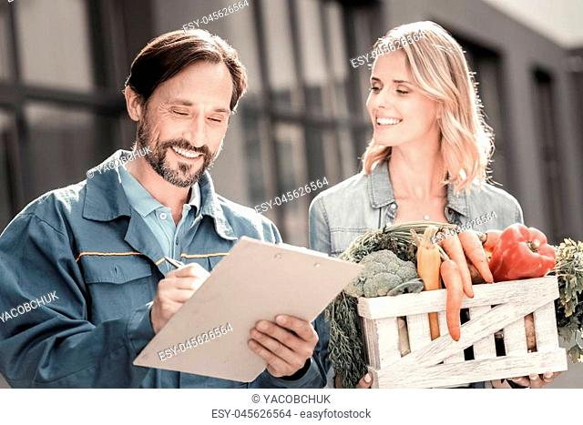 Great service. Joyful positive young woman standing near the delivery man and holding a box with vegetables while looking at him