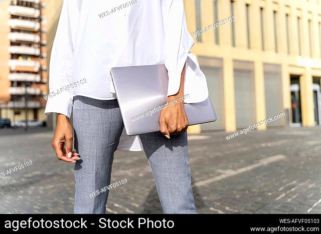 Businesswoman in the city, carrying laptop