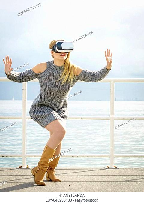 Young woman testing VR glasses outside. Female wearing virtual reality headset during spring weather