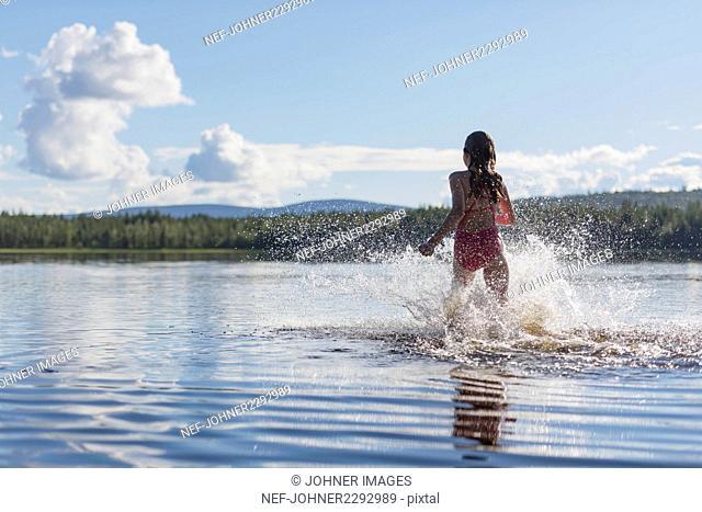 Girl running in lake