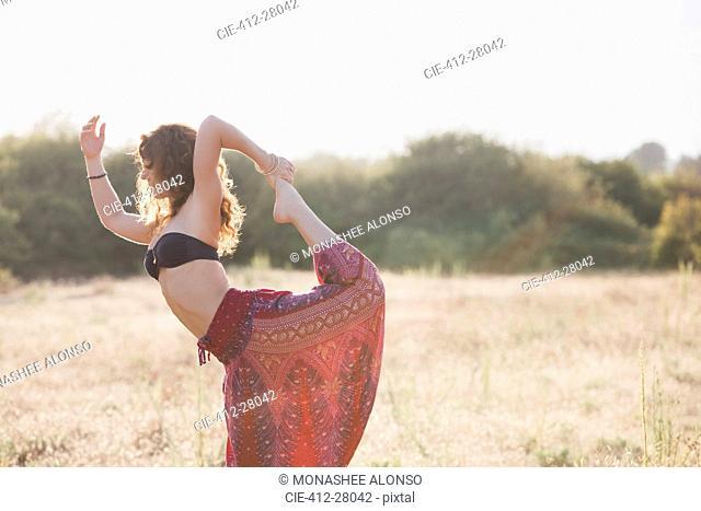 Boho woman in king dancer yoga pose in sunny rural field