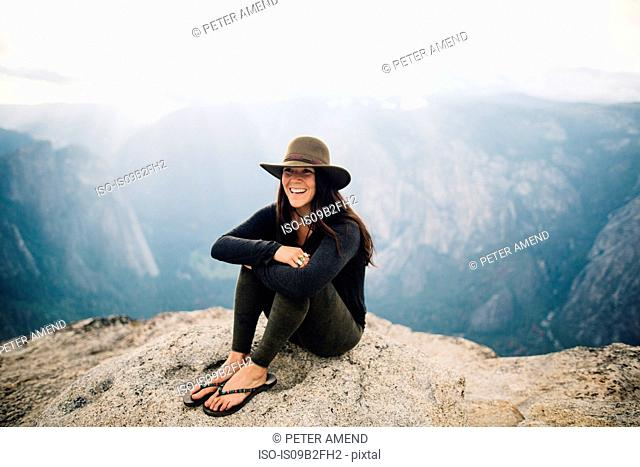 Portrait of young woman sitting at top of mountain, overlooking Yosemite National Park, California, USA