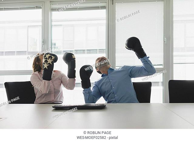 Cheering businesswoman and businessman wearing boxing gloves in office