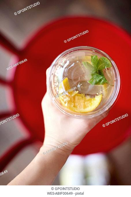 Woman's hand holding glass of lemonade, top view