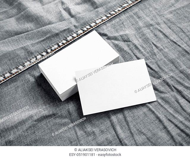 Blank white business cards on gray denim background