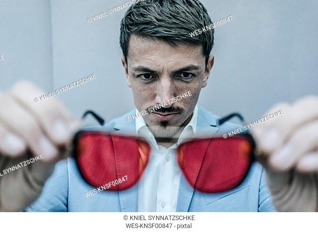 Businessman holding sunglasses