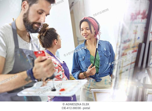 Artists talking and painting in art class studio