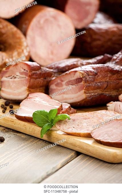 Various types of meat and bacon on a wooden board