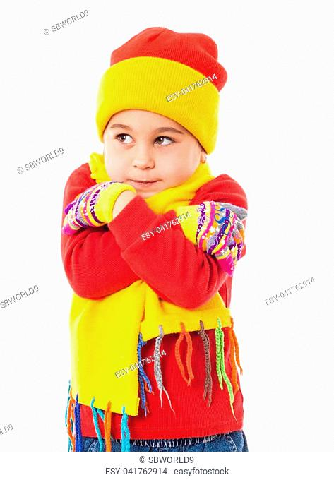 A girl in winter clothes who looks frozen, isolated on white