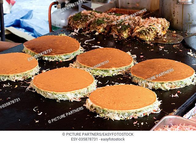 Tokyo, Japan - May 14, 2017: Baking pancakes at a grill, Okonomiyaki, at the Kanda Matsuri Festival