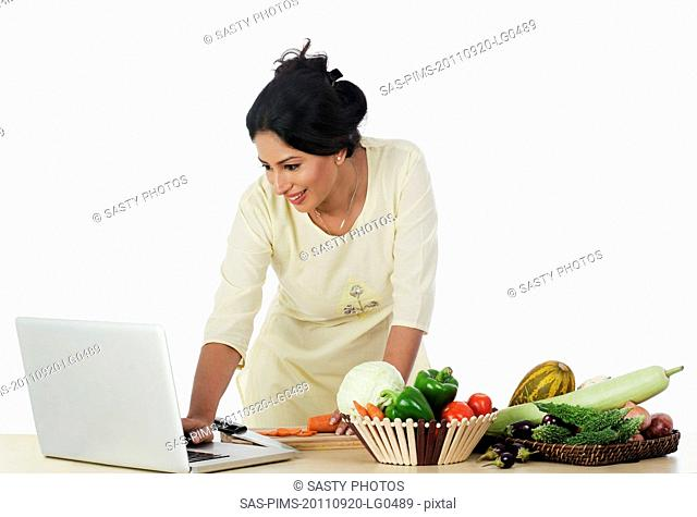 Woman cutting vegetables and using a laptop