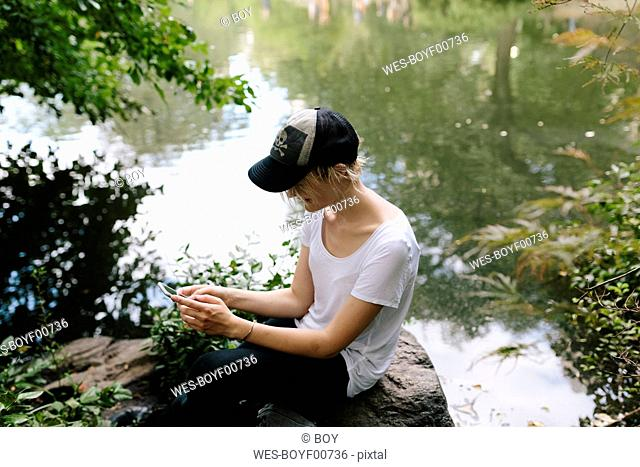 Young woman sitting at lakeside in park looking at cell phone