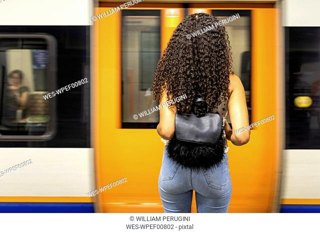 UK, London, rear view of young woman waiting at underground station platform
