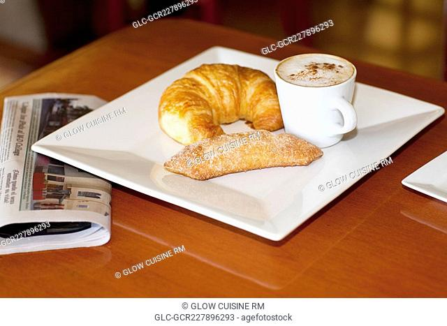 High angle view of a croissant and sugar cracker with a cup of coffee