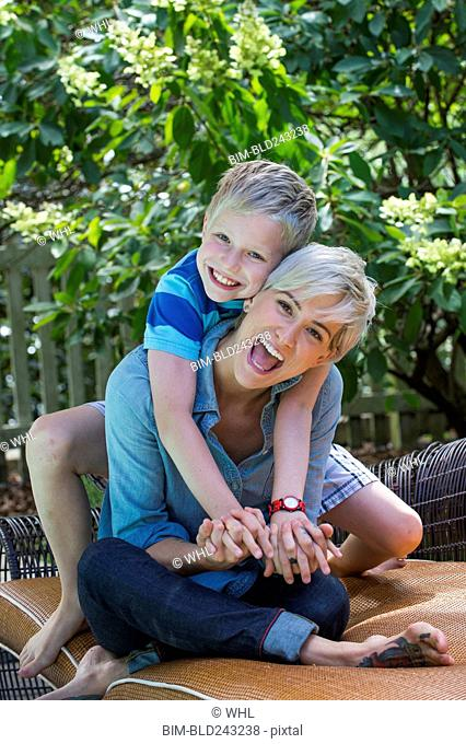 Caucasian mother and son playing on sofa outdoors