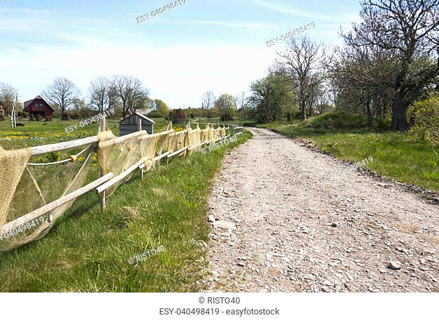 Village road and a fence with fishing nets in Saaremaa, Estonia