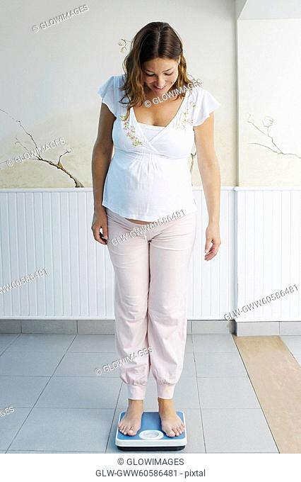 Pregnant young woman standing on a weighing scale