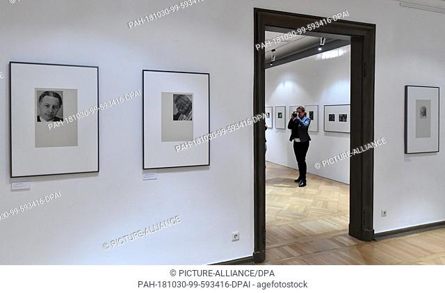 "30 October 2018, Thuringia, Gera: A woman photographs the photographs in the special exhibition """"...committed to objectivity"