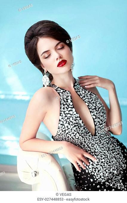 Elegant lady. Makeup. Hairstyle. Jewelry. Brunette sensual woman in fashion gems dress posing on modern armrest sofa over blue background
