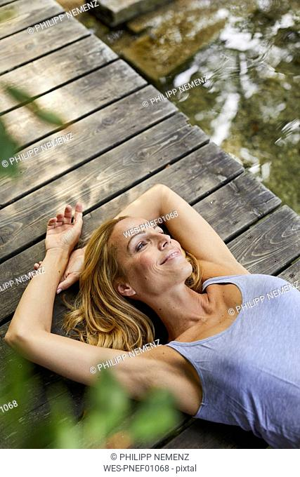 Smiling blond woman lying on wooden jetty at a lake