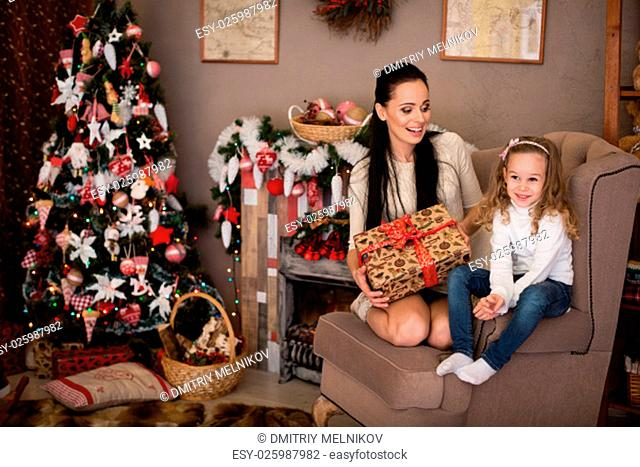 Happy family with gifts sitting near Christmas tree at home. Merry Christmas and New Year