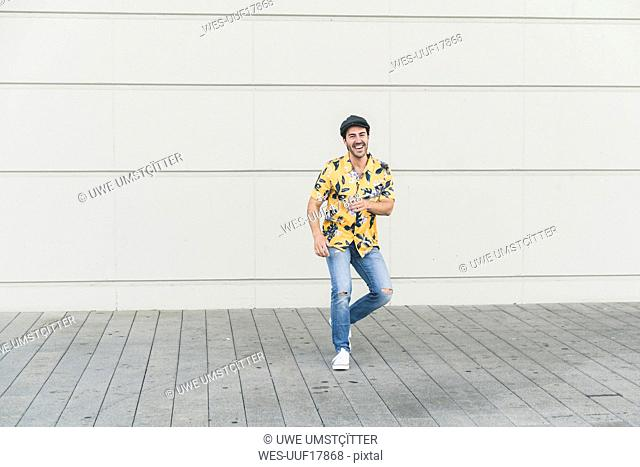 Young man wearing flat hat and aloha shirt, having fun