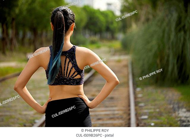 Rear view of woman on railway track, hands on hips
