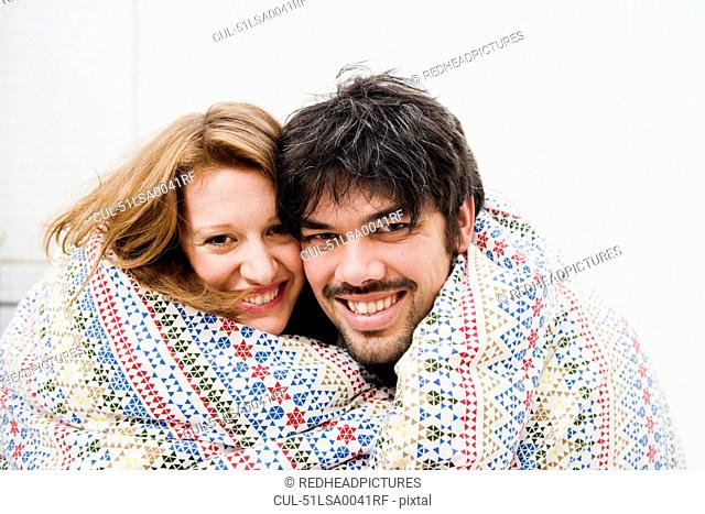 Smiling couple wrapped in blanket