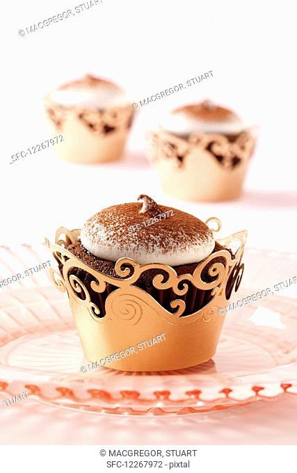 One Devil s food chocolate cupcake on a pink plate with two others in the background on a light pink cloth