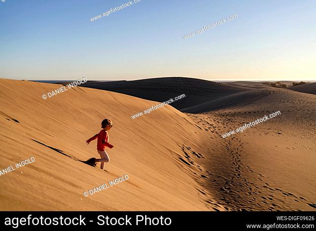 Girl running down sand dune, Gran Canaria, Spain