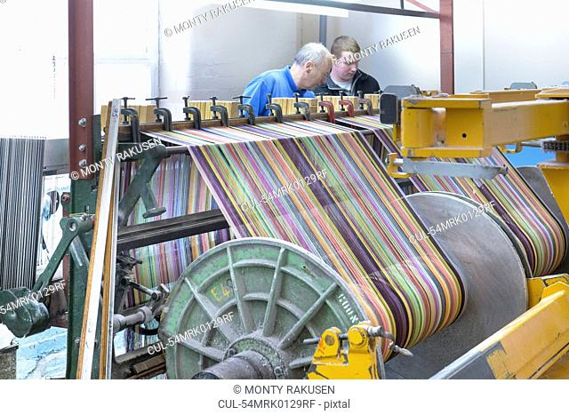 Worker using looms in textile mill