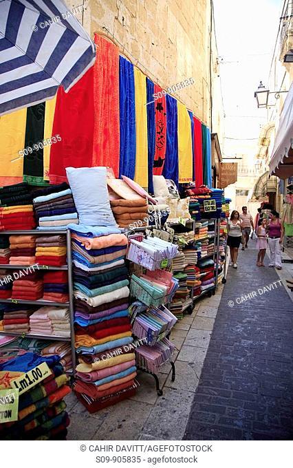 Malta, Gozo, Victoria, Rabat, colourful side street stall selling towels
