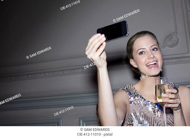 Well dressed woman with champagne taking self-portrait with camera phone