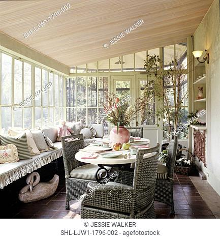 PORCHES: Enclosed sun porch with eating area, window seat with ruffled cushion and pillows, french doors lead to a conservatory