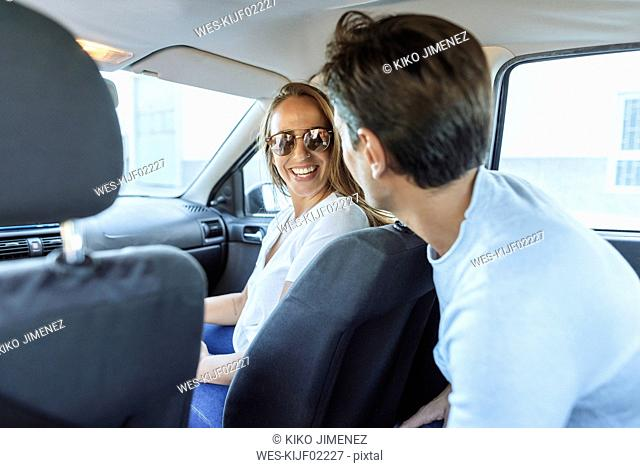 Happy couple in car with man on back seat and woman on front passenger seat