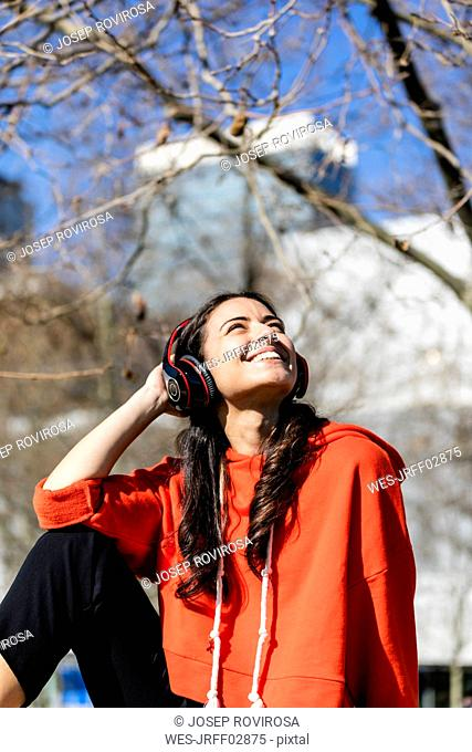 Young contemporary dancer wearing red hoodie shirt, sitting and listening to music
