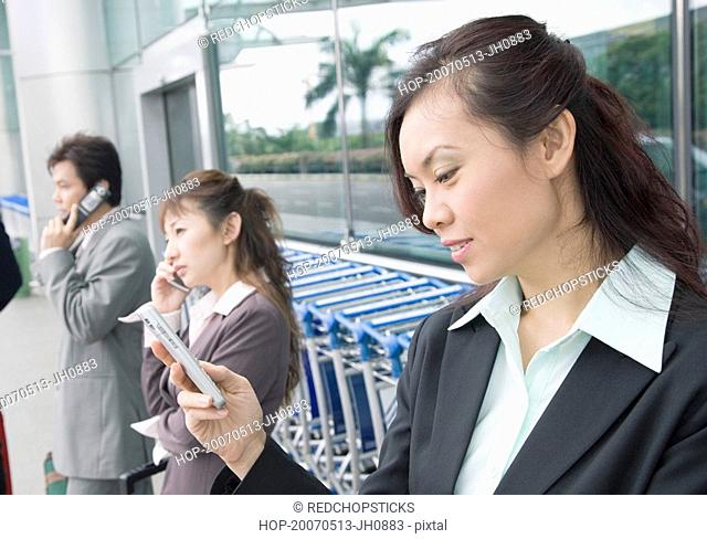 Two businesswomen with a businessman waiting at an airport lounge