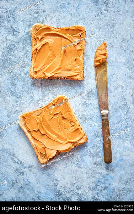 Two tasty peanut butter toasts placed on stone table. Knife on side. Top angle shot with copy space