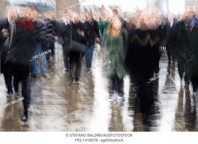 Blurry image of commuters on London Bridge, London, UK, early morning on a winter day