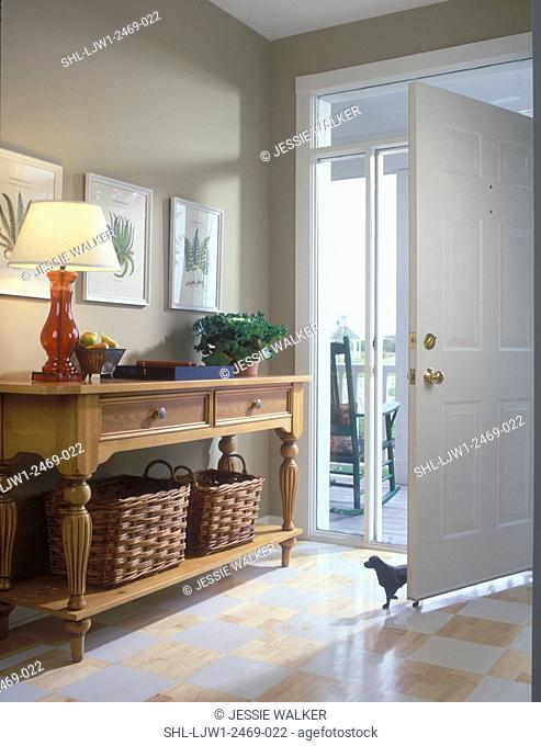 ENTRY HALL: Transom and sidelight windows in front door entry, painted checkerboard wood floor, hall table with botanical prints and storage baskets underneath