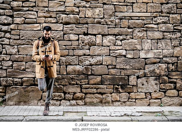 Spain, Igualada, man standing at stone wall using cell phone