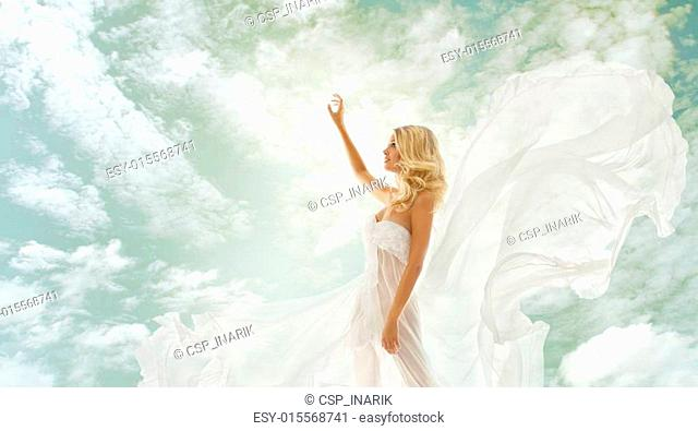 woman blonde in fluttering white dress with flying fabric, beautiful girl showing advertise on sky