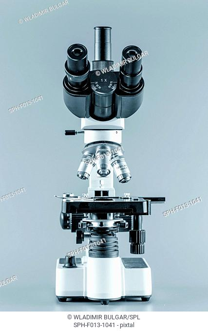 Trinocular microscope against a grey background