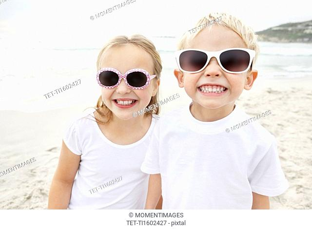 Portrait of brother 4-5 and sister 10-11 wearing sunglasses on beach
