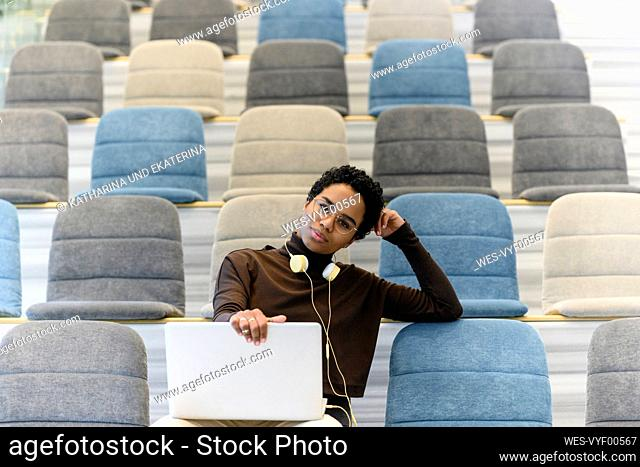 Curly haired woman using laptop at auditorium