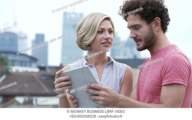 Young couple standing on rooftop with urban skyline in background, using digital tablet to take photograph.Shot on Sony FS700 in PAL format at a frame rate of...