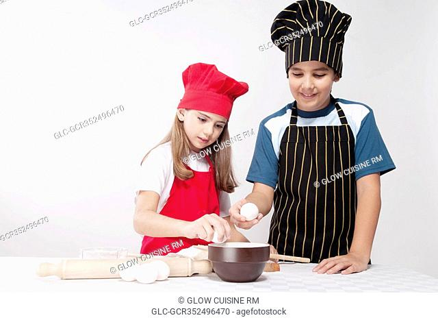 Boy preparing a cake with his sister